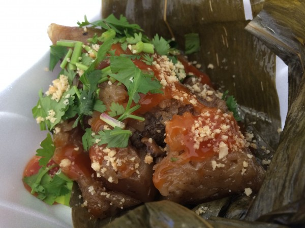 """Zong zi"" - rice dumpling stuffed with pork belly, beef, and topped with a sweet and sour sauce, wrapped in banana leaf"