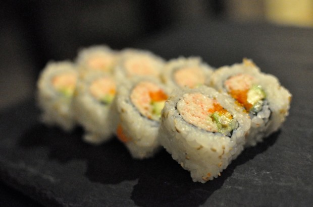A fabulous California roll, stuffed with krab salad, sliced avocado, fresh, crisp cucumber, fish roe,  and sprinkled with sesame seeds on the outside