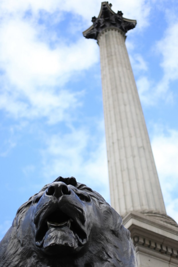 Staring up the lion statue towards the sky and Nelson's column at Trafalgar Square, which commemorates the Battle of Trafalgar, a British naval victory of the Napoleonic Wars over France and Spain