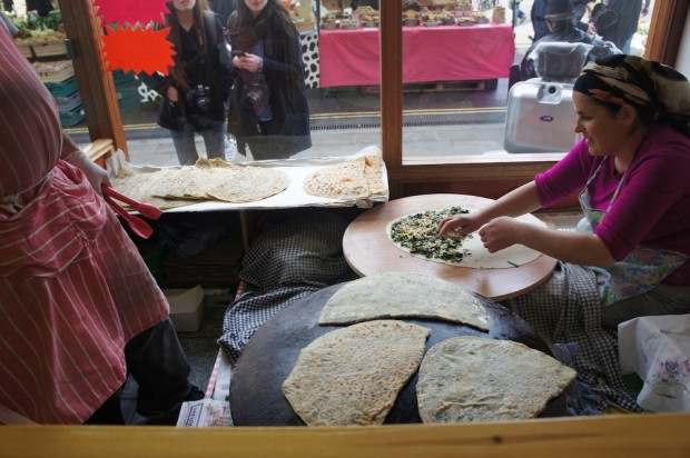 A Turkish lady and man make gozlenes, kind of a Turkish roti stuffed with cheese and spinach