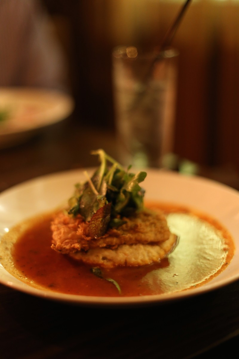 Country fried red fish with grits in a tomato sauce