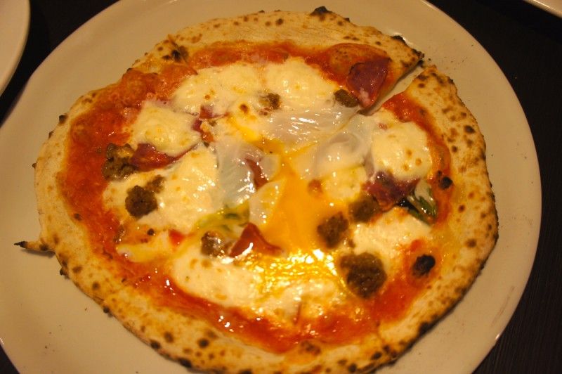 Margherita pizza with sausage, salami, and topped with egg