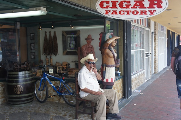 Cigar factory man sitting outside inviting folks in to pick up some cigars. Uncanny resemblance to the wood carving of a cigar smoking man on a chair in the glass display case.