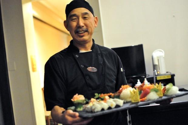 Chef Yoshi presenting a special sushi plate full of nigiri, sashimi, and a maki roll
