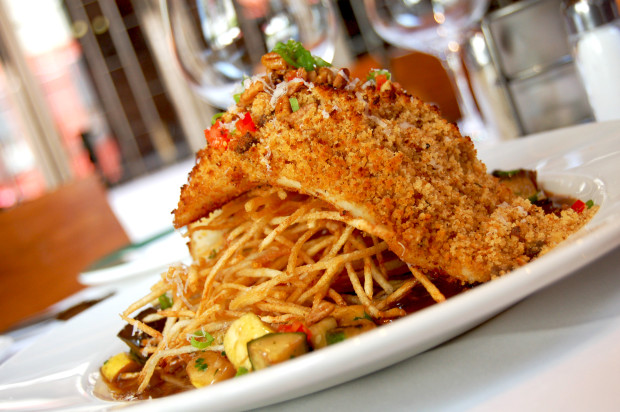 Andouille crusted fish of the day with shoestring potatoes, zucchini, squash and Creole meuniere sauce at Emeril's.