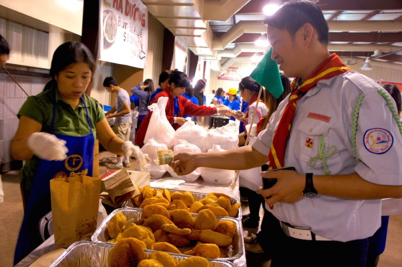 A Vietnamese Catholic boy scout buys some banh tieu